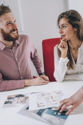 Young smiling couple in real estate agency office